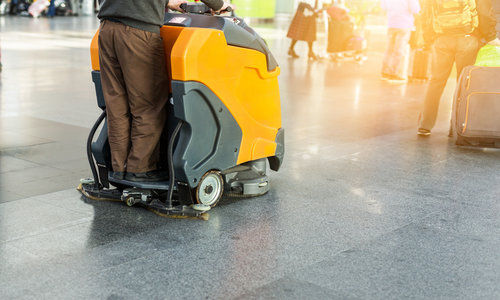 Man driving professional floor cleaning machine at airport or railway station.