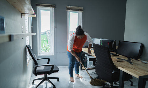 Young Woman Cleaning Floor In An Office.